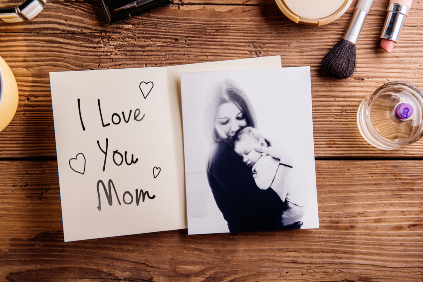 Mothers day composition. Black-and-white picture of mother holding her little baby, greeting card with I love you Mom text and various cosmetics. Studio shot on wooden background.